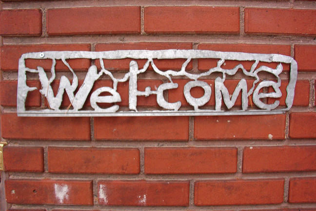 "Metal ""Welcome"" sign on red brick wall"