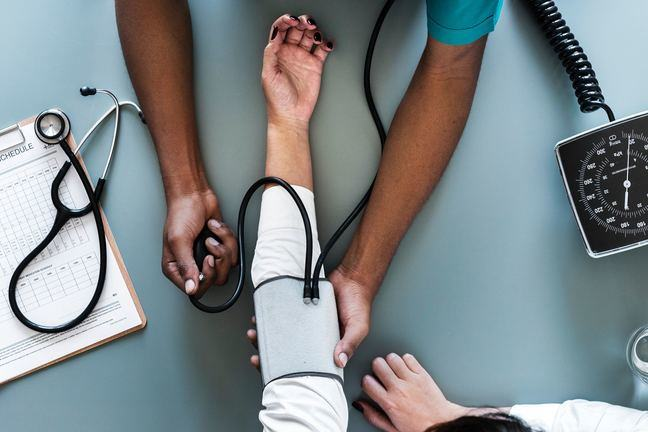 aerial view photography of person holding arm while pressing blood pressure machine