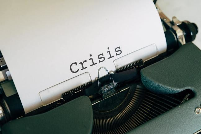 "the word ""crisis"" printed in a white A4 sheet"