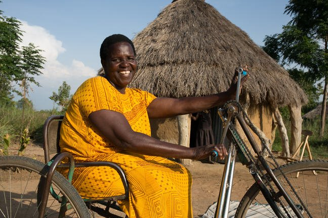 The photo shows Margaret Among, 45, Amuria district, Uganda, using her wheelchair outside her house