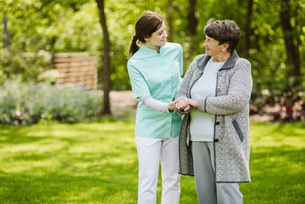 Female nurse and an elderly lady are walking together outside