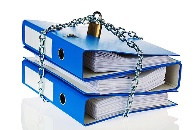 Two large blue folders that are sitting on top of each other with a padlock and chain around them so they are 'locked'