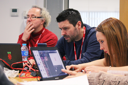 A photograph of people programming at laptops