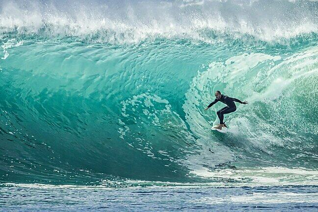 A surfer inside the tube of a large wave.