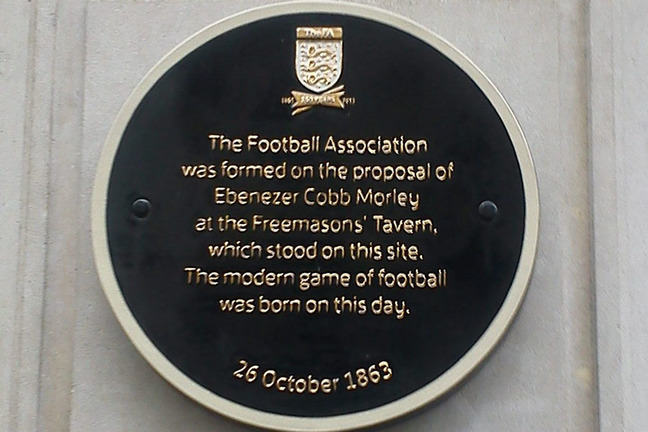 Round metal plaque with the words 'The Football Association was formed on the proposal of Ebernezer Cobb Morley at the Freemason's Tavern, which stood on this site. The modern game of football was born on this day. 26 October 1863'