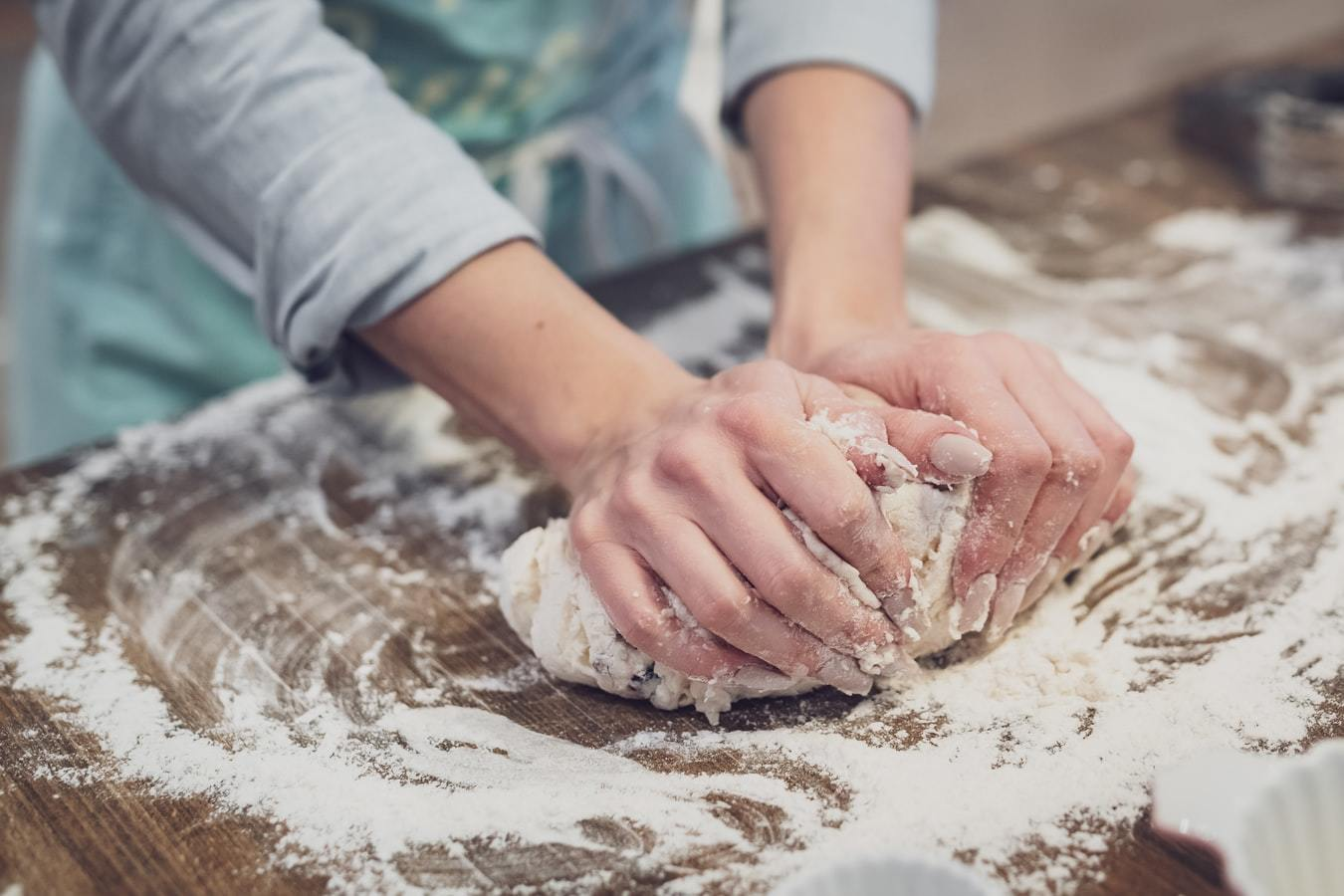 a person standing and making dough