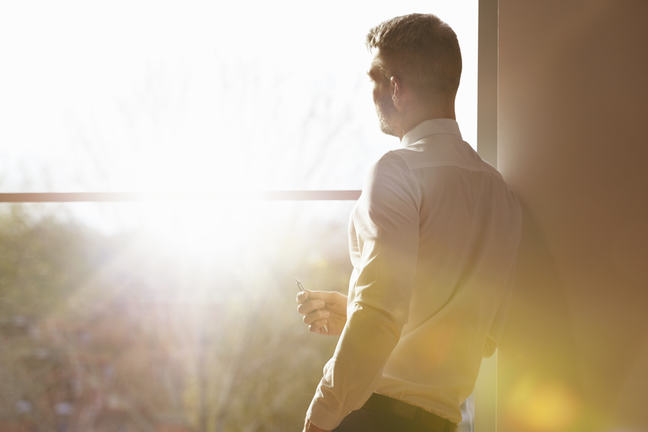 Man standing by window with sunlight