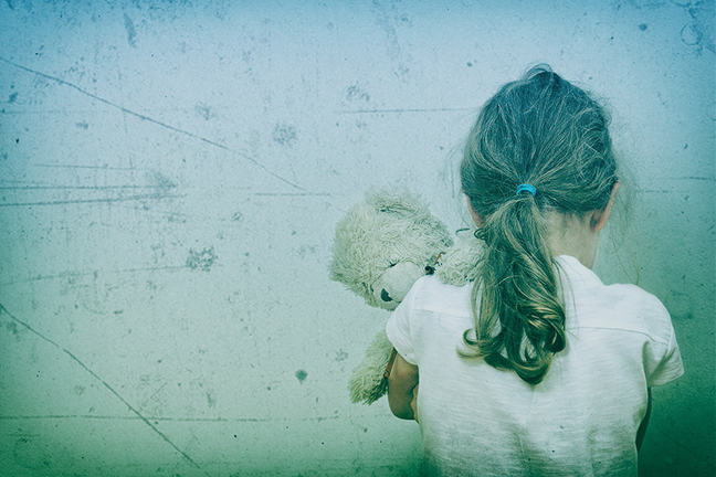 Little girl facing the wall crying