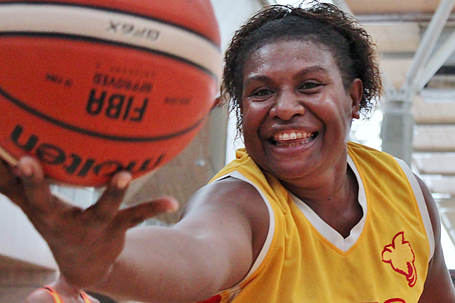 a female coach reaches out with a basketball, Papua New Guinea