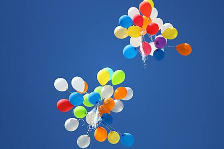 Two large bunches of multicoloured balloons floating away into the sky - viewed from below on a clear day.