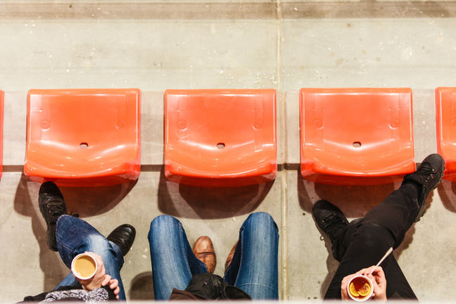 Row of plastic chairs and legs in football stadium