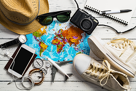 Travel items are scattered on white wooden floor boards. The items include a sunhat, sunglasses, a map, iphone, wrist watch, camera, notebook, miniature plane, compass, earphones, and yellow tinted converse runners.