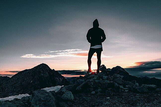 A mountain runner looks out from a peak at sunrise