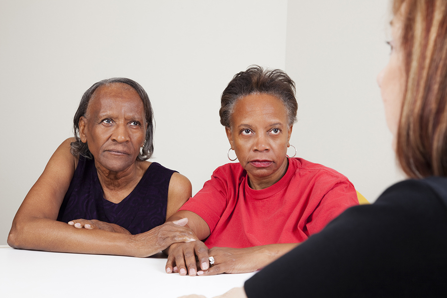 Serious african-american mother and daughter talking with a care worker