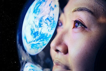 A woman in space looking at the reflection of Earth on her astronaut helmet.