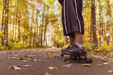 A person's feet and legs on a skateboard on a path surrounded by trees.