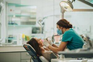 a dentist using instruments to give a woman dental treatment