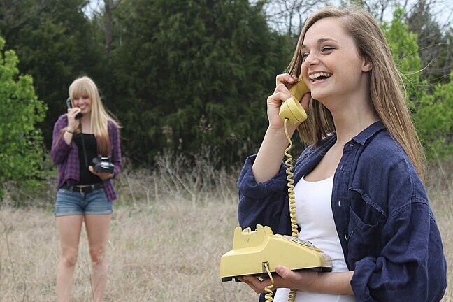 Two women in a field talking to one another on old-fashioned land-line telephones