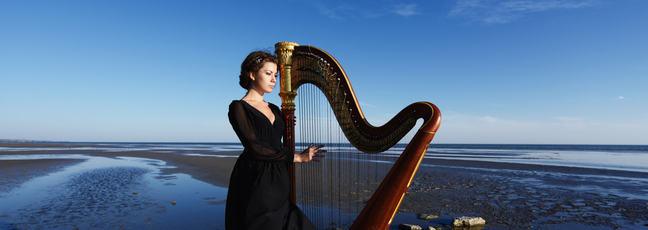 lady holding harp on Irish beach in the early evening