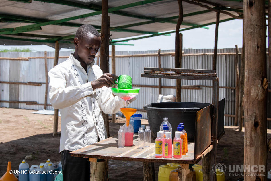 Man, called innocent Havyarimana, a refugee soap maker, is pouring hand sanitiser into smaller bottles.