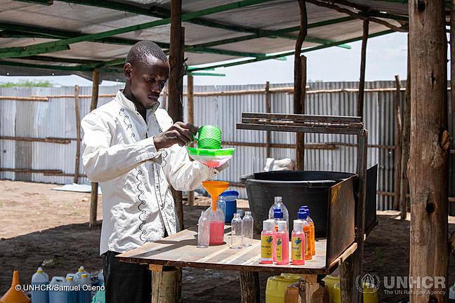 Man, called innocent Havyarimana, a refugee soap maker, is pouring hand sanitiser into smaller bottles.