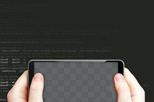Hands holding a mobile phone in front of a screen of code, representing how you can learn Java with this online programming course
