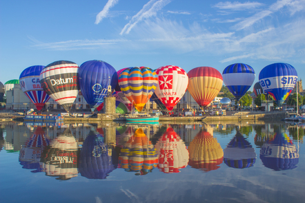 Hot air balloons hovering on the ground by the river Avon