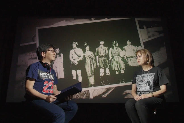 Prof. Ohwada is interviewing with Ms. Mari Kotani in front of the screen showing Cos-Play in early days
