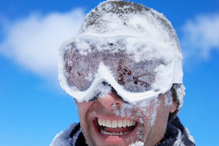 Man smiling with snow in his face