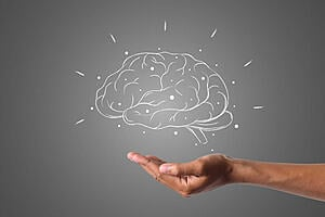 drawing of a brain hovering above an open hand