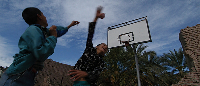 Two children playing basketball.