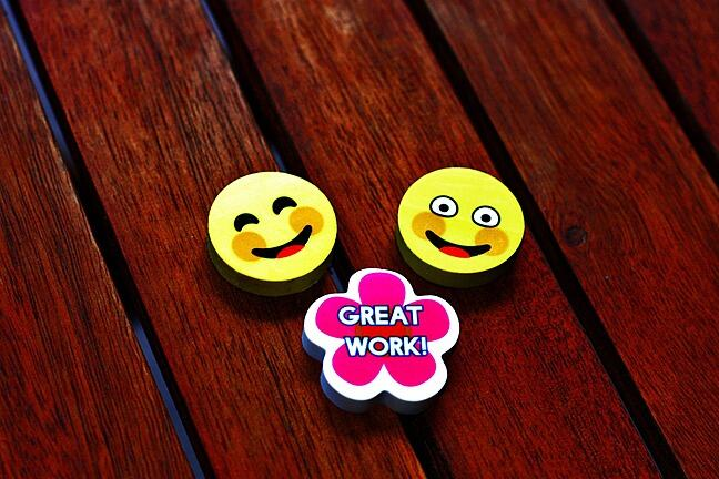 Two smiling emoji faces and a great work badge sitting on a table