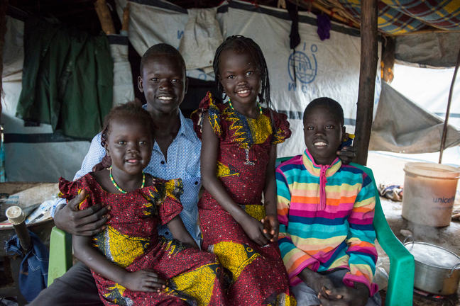 An African family of a teenage boy and three young girls are in accommodation that resembles a tent. Two girls that might be twins are sitting one of each knee of the boy and the third girl is sitting next to them. They are all smiling at the camera.