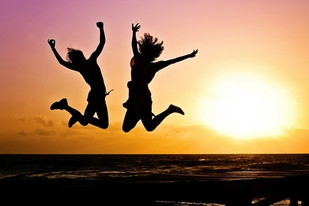 two people jumping in front of sunset