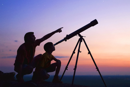 Photo of two people looking through a telescope