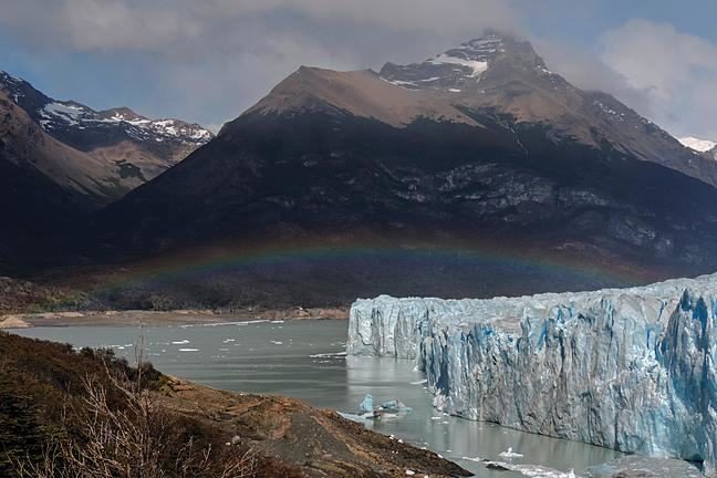 Image of a glacier front, water, mountains and a rainbow