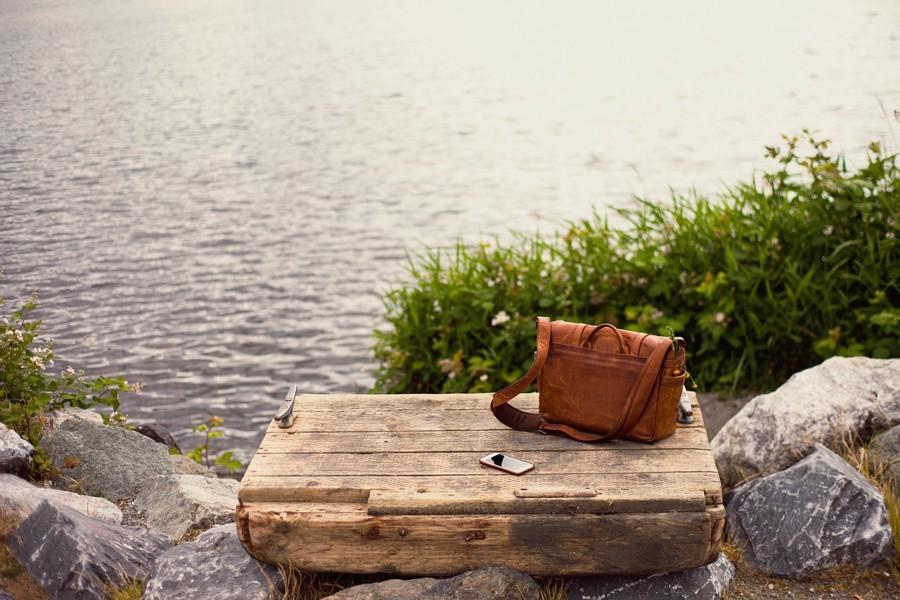 A bag and a phone on a board at a water's edge