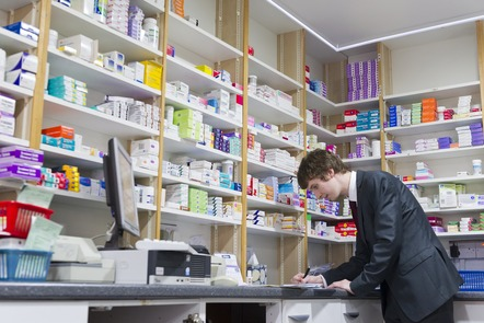 Pharmacist and shelves of medicines