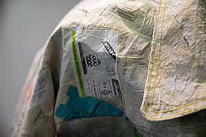 The shoulder and collar of a shirt made up of recycled patchwork fabric