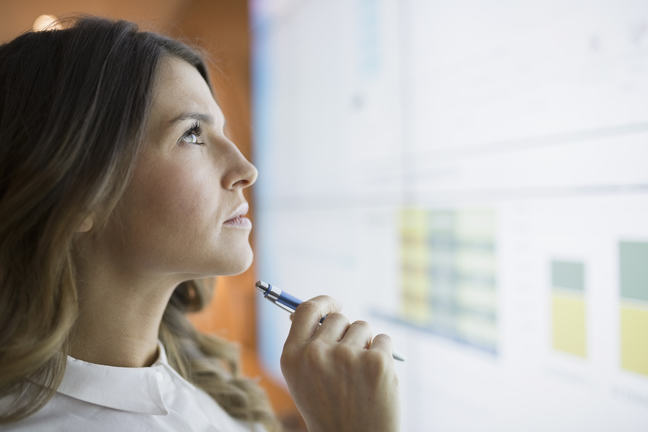 Woman with a pen in hand deciphering data