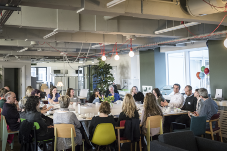 Photograph of a large group of people having a meeting around a big table