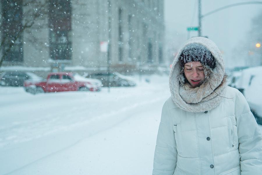 Teenage girl walks through snowfall in the street in Manhattan