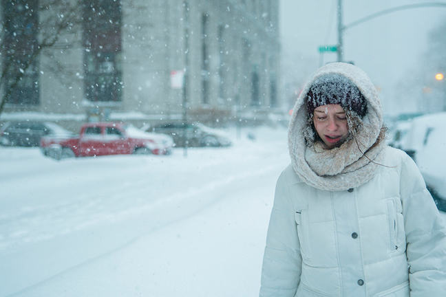 Teenage girl walks through snowfall in the street in Manhattan