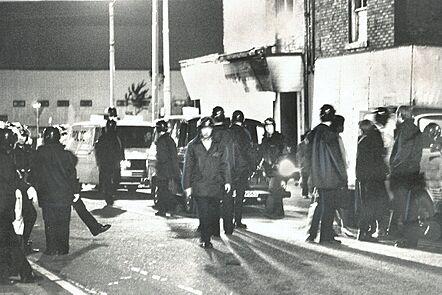 A photograph of around 15 policemen crowding around the destruction caused by the Moss Side Riot