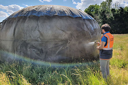 A person spraying a lightweight storage / water tank in a field. Image from Deploy Tech Ltd.