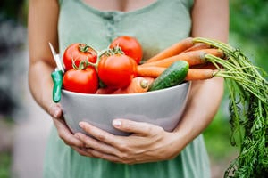 Woman standing with large bowel of fresh vegetables.