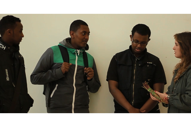 A still from the film 'Khat' shows the interviewer talking to three young men about their opinions of the substance. She holds a stick of Khat.