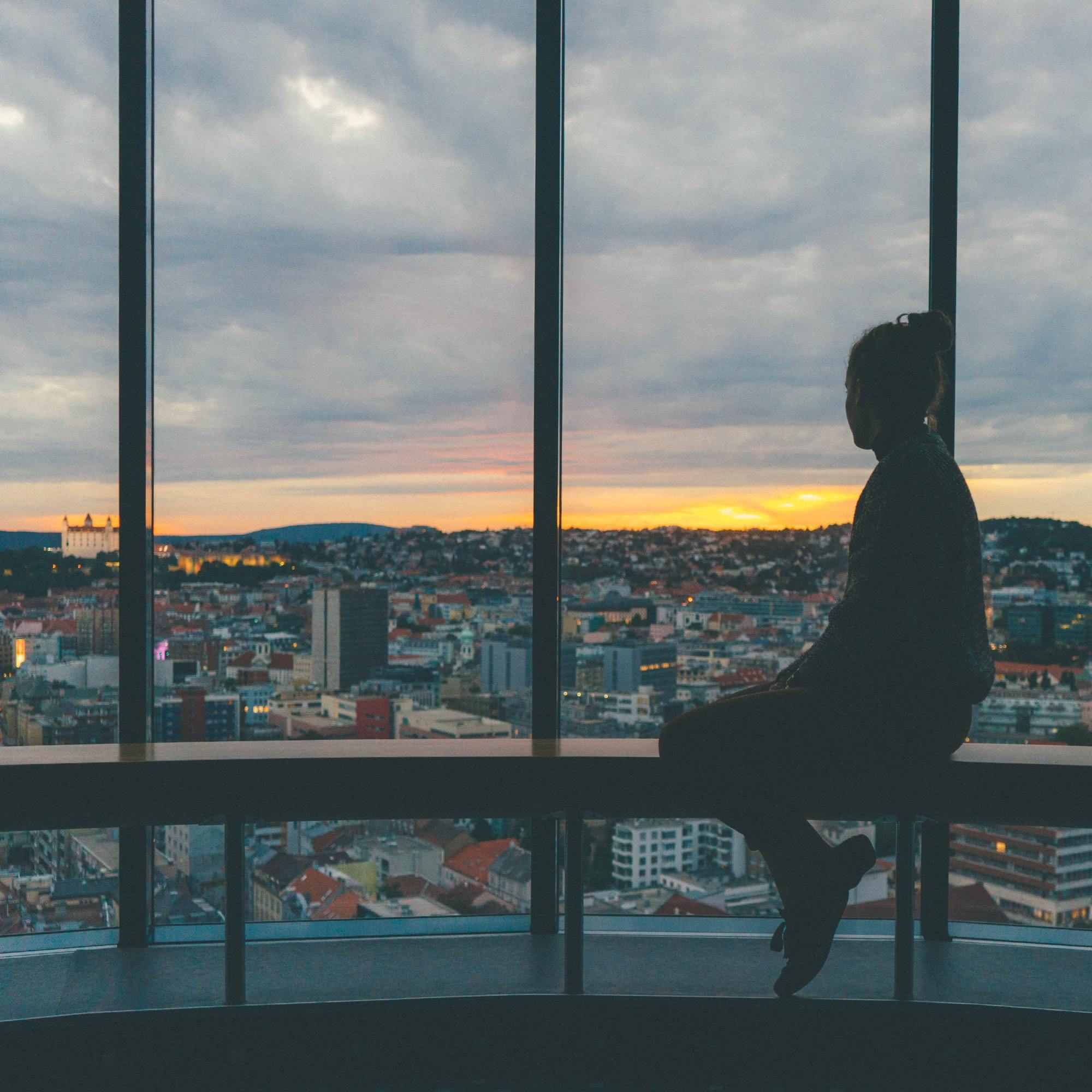 Woman looking out of a large window over a cityscape