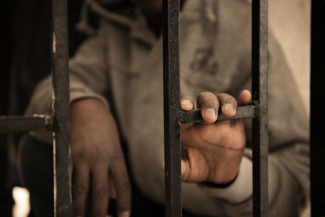 A teenage boy stands behind metal bars with his left hand resting on the bars. We cannot see his face and his hands are the main focus of the picture.