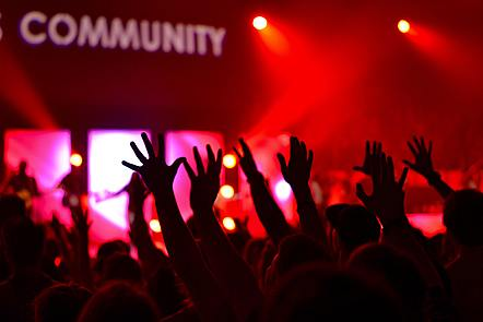 The word 'community' appears in large letters above a large number of upstretched hands at a rave or club event